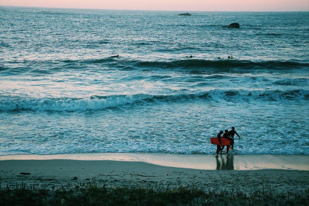 surfeurs à l'eau au crépuscule